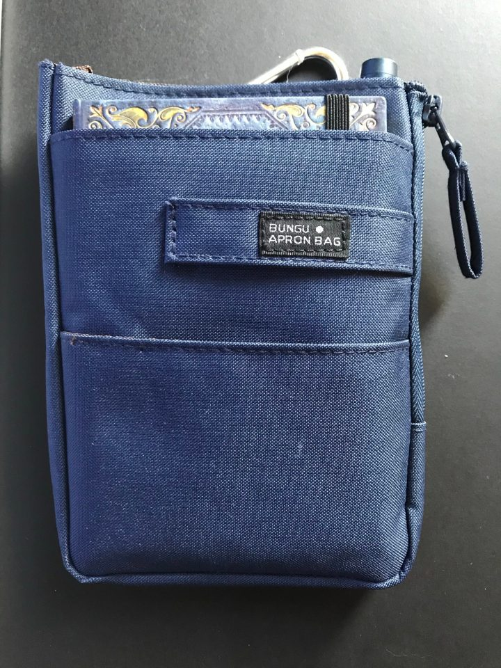 Photo of a belt bag with notebook and fountain pen inside.