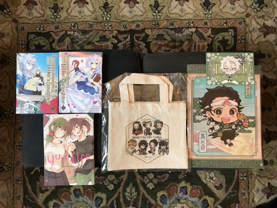 """Photo of three manga and """"Demon Slayer"""" merchandise from Kinokuniya."""