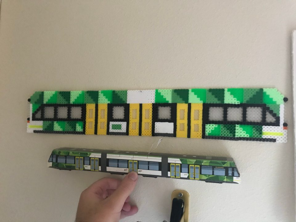 Photo of a Melbourne E-Class tram made of perler beads side-by-side with a papercraft one.