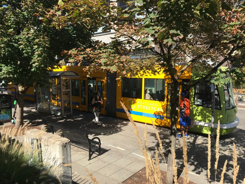 Photo of a green and yellow Portland Streetcar train behind autumn leaves at NW 13th and Lovejoy.