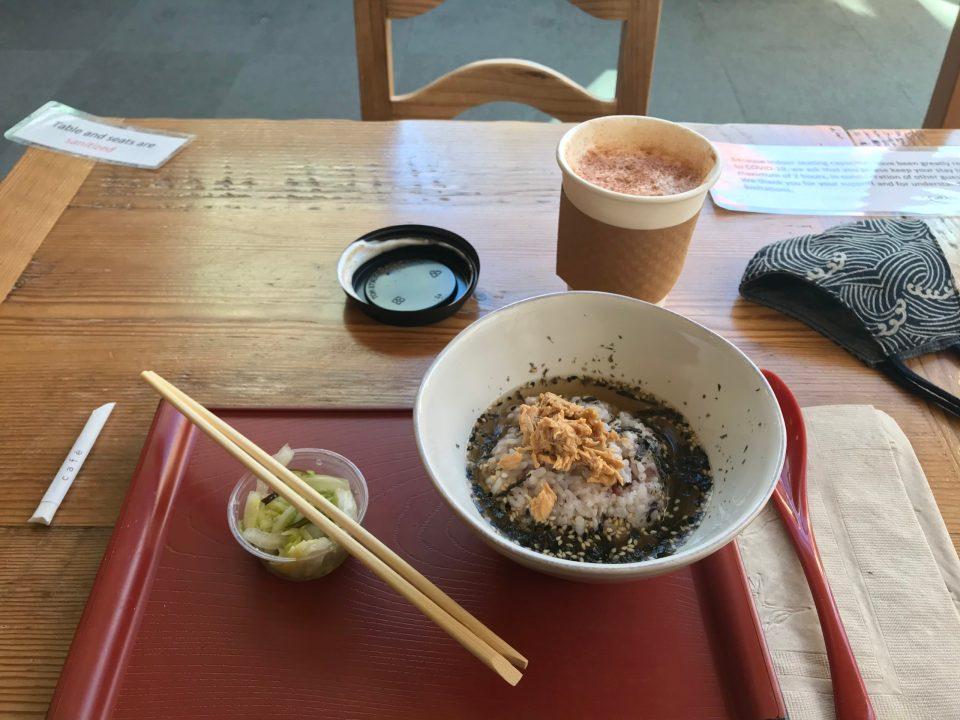 Photo of a chazuke on a red tray and Hojicha Chai latte on a table.