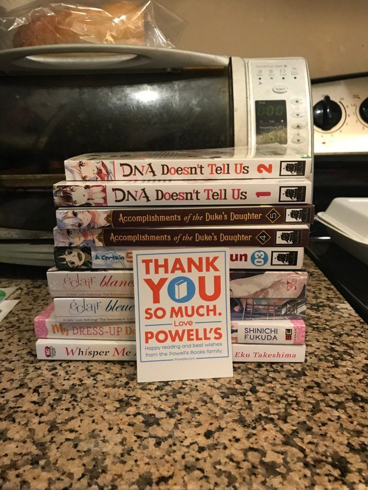 Photo of a stack of books from Powell's books with a thank you card.