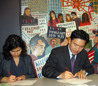 Martha Chavez and S.J. Jung signing letters to President Obama