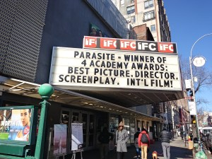 """A black and white marquee celebrating the Oscars win of the movie """"Parasite."""""""