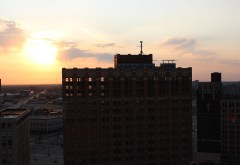 A building in shadow in Detroit, with the sun behind it.