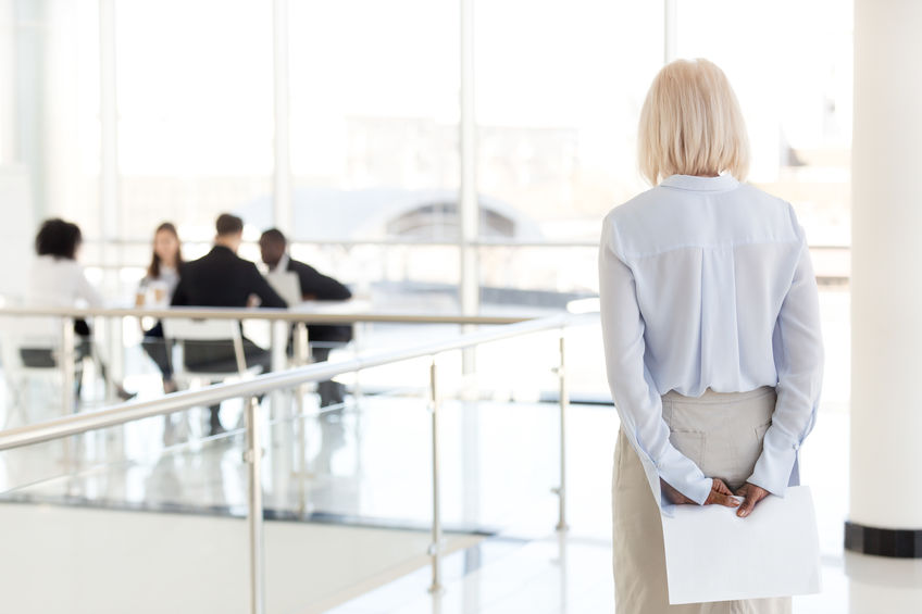 Older woman at work on outside of group of coworkers
