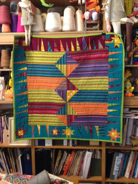 Turquoise, lime green, purple, orange, maroon, and gold quilt hanging in artist studio