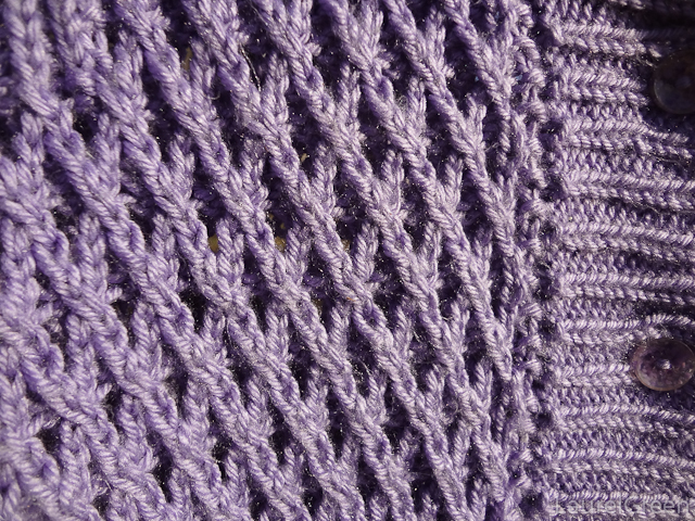 a close-up photo of a diamond cable eyelet stitch