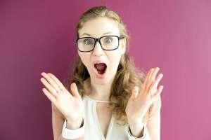 FibroFee macht eine Ankündigung über Presse, Kooperationen und Angebote. Auf dem Bild ist der Oberkörper einer jungen Frau mit Brille und blonden Locken zu sehen. Sie steht vor einer dunkelrosa Wand und trägt ein weises Top. Ihre Augen und der Mund sind weit geöffnet, ihre beiden Hände streckt sie mit der Handfläche zum Betrachter in die Höhe. Ihr Gesichtsausdruck spiegelt freudige Überraschung wider.