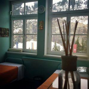 Das Bild zeigt einen Ruheraum im Gasteiner Heilstollen. Im Vordergrund des Bildes steht ein Duftspender, aus dem Holzstäbchen ragen. Im Raum mit türkisfarbener Wand stehen zwei Betten. Ein Doppelfenster gibt den Blick auf den gegenüberliegenden Berghang frei.