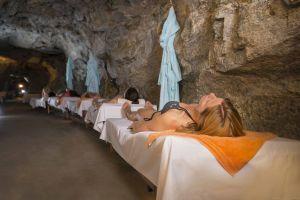 Zu sehen ist ein Gang im Inneren des Gasteiner Radon-Stollen, der in den grauen Fels gehauen ist. Rechts, längs des Gangs stehen aufgereiht Holzliegen, auf denen Frauen in Badekleidung auf dem Rücken liegen.
