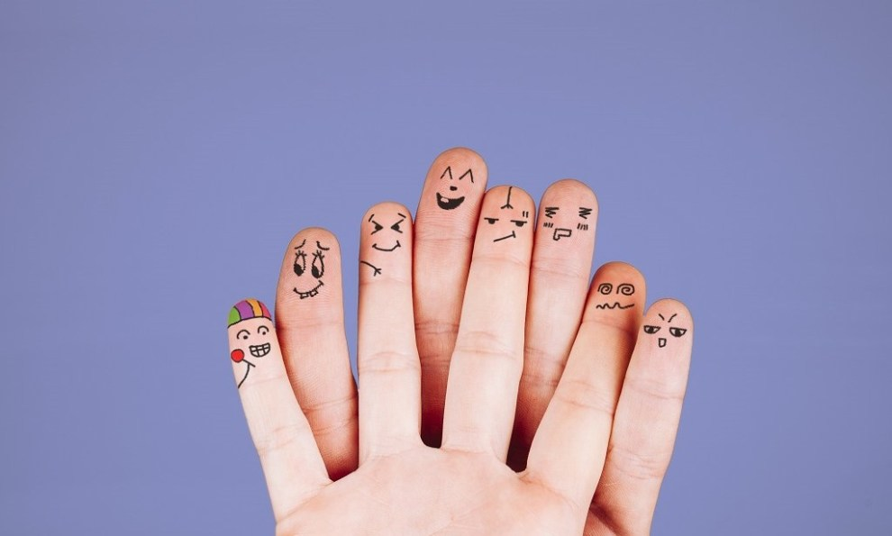 Das Bild zeigt die Innenseiten von Fingern von zwei übereinander gelegten Händen. Auf die Fingerkuppen sind Gesichter gemalt: manche freundlich, andere mürrisch, manche jung, andere älter.