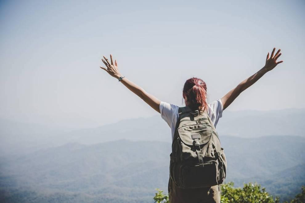 Symbolbild zur Krankheitsbewältigung - Junge Frau steht mit dem Rücken zur Kamera und schaut über ein Tal. Sie hat beide Arme erhoben und trägt einen großen Rucksack.