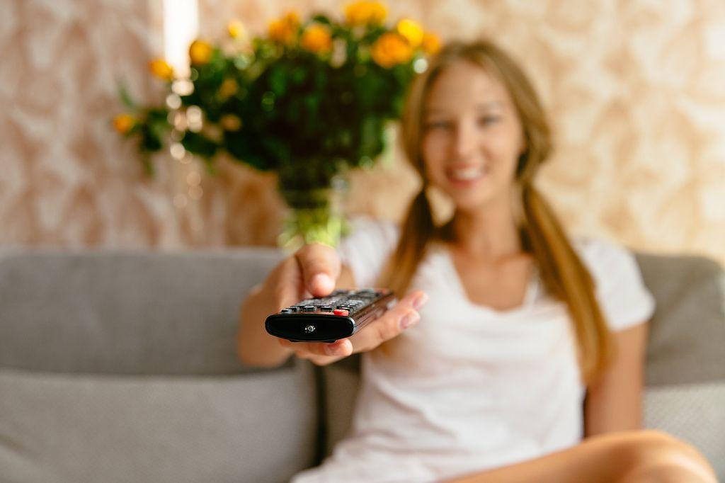 Das Foto zeigt eine junge Frau, die auf einem Sofa sitzt und in der rechten Hand eine Fernbedienung hält. Im Hintergrund ist ein Strauß Blumen zu sehen.