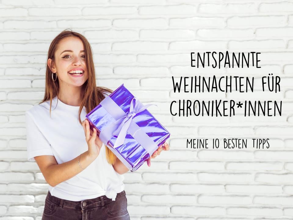 Entspannte Weihnachten für Chroniker*innen - meine 10 besten Tipps: Eine junge Frau lächelt in die Kamera und hält ein Paket in der Hand. Sie steht vor einer Backsteinmauer.