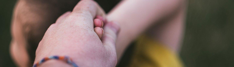 Kuvituskuva, jossa miehen käsi pitää kiinni lapsen kädestä. Läntinen syöpäkeskus palvelee sinua. Me olemme täällä sinua varten – olet sitten syöpäpotilas, tutkija tai Syöpäkeskuksen työntekijä.