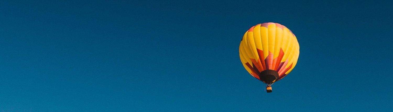 Kuvituskuva, jossa kuumailmapallo lentää sinisellä taivaalla. Muista pitää huolta itsestäsi – syöpä laittaa usein sairastuneen arjen ja suunnitelmat uusiksi.