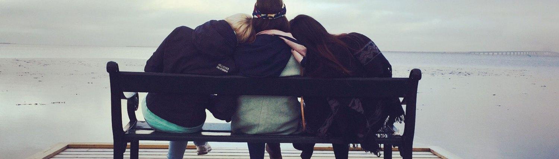 Kuvituskuva, jossa kolme naista istuu laiturilla olevalla penkillä. Myös syöpään sairastuneen läheiselle on tarjolla tukea.
