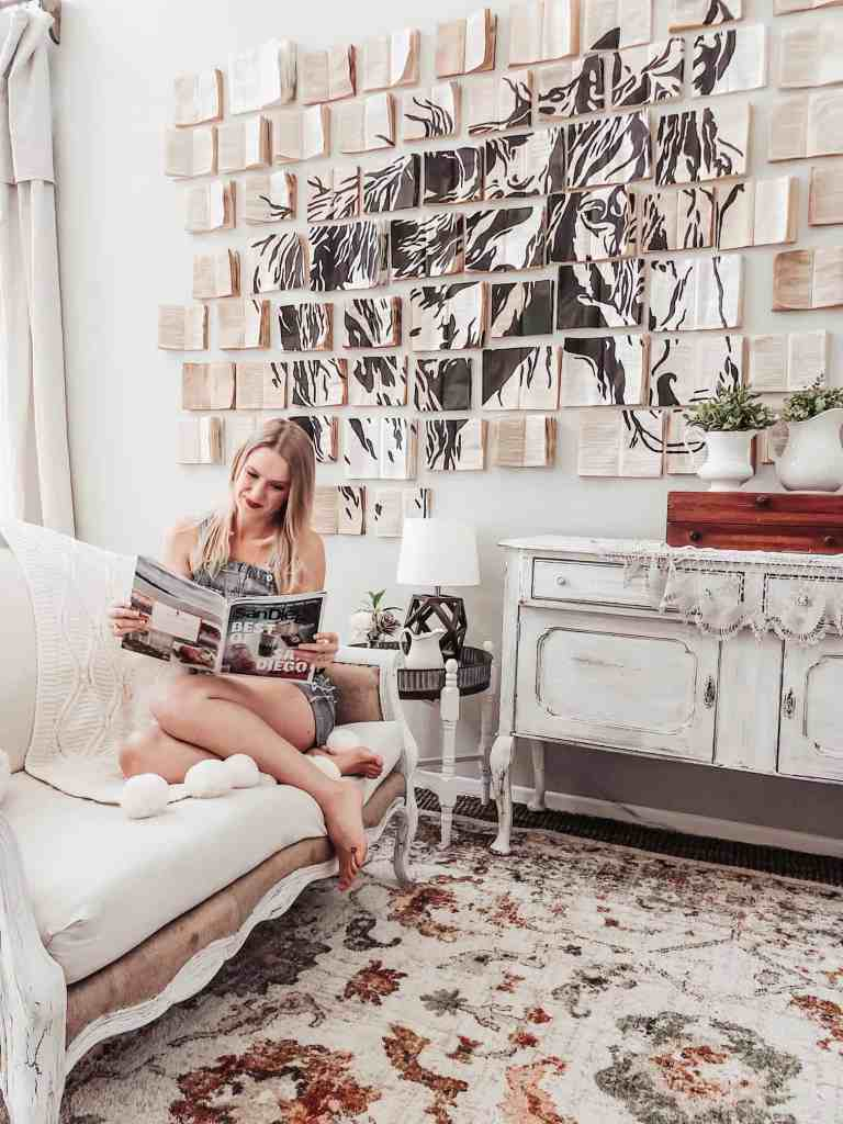 girl sitting on couch reading magazine with vintage book wall art installation in background