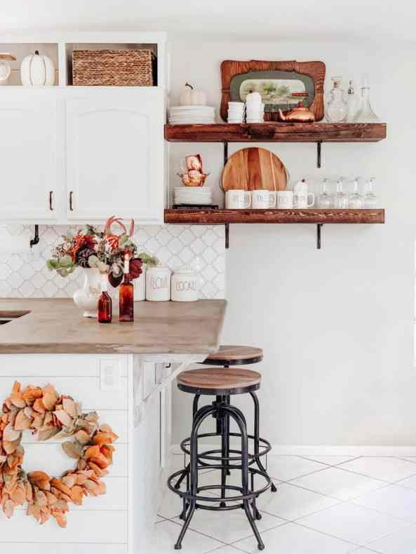 farmhouse style kitchen with white cabinets and open wood shelving