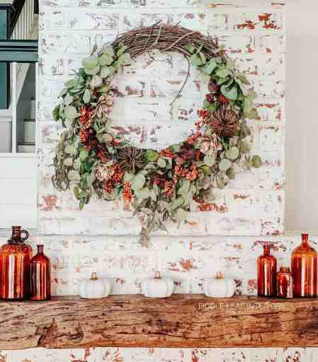diy live eucalyptus wreath styled for fall with faux berries and pumpkins