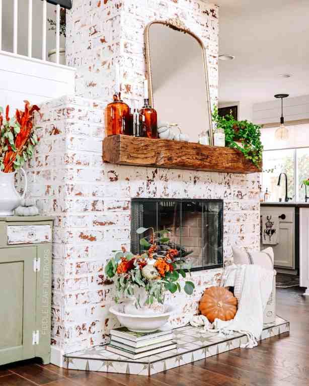 german schmear fireplace decorated for fall with amber bottles, pumpkins, and fall floral arrangement - Fall Home Tour