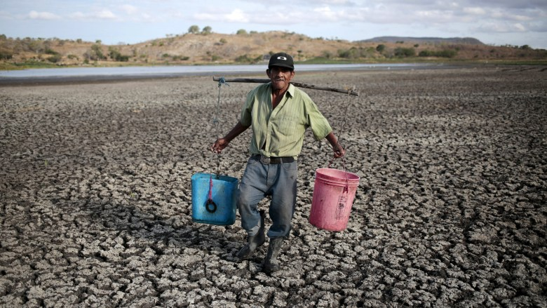 A farmer carries buckets of water in Playitas town