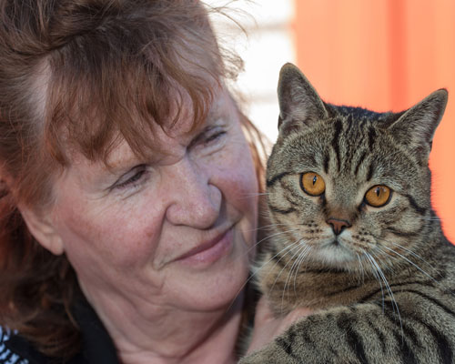 A woman holding a tabby cat