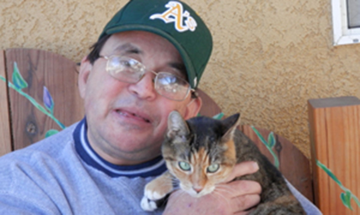 Volunteer Jared holding his beloved calico cat, Hot Rod.