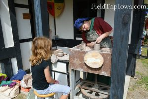 A child watching a demo at The Potter's House at the Renaissance Faire at Sleepy Hollow