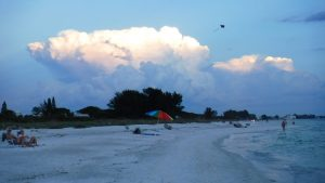 People enjoying the beach during sunset at Bean Point on Anna Maria Island Florida.