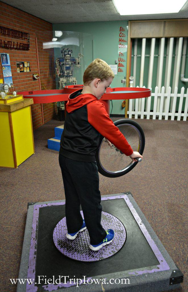 Boy spins at Bluedorn Science Imaginarium in Waterloo Iowa.
