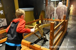 Boy tries to plow at John Deere Tractor And Engine Museum in Waterloo Iowa.