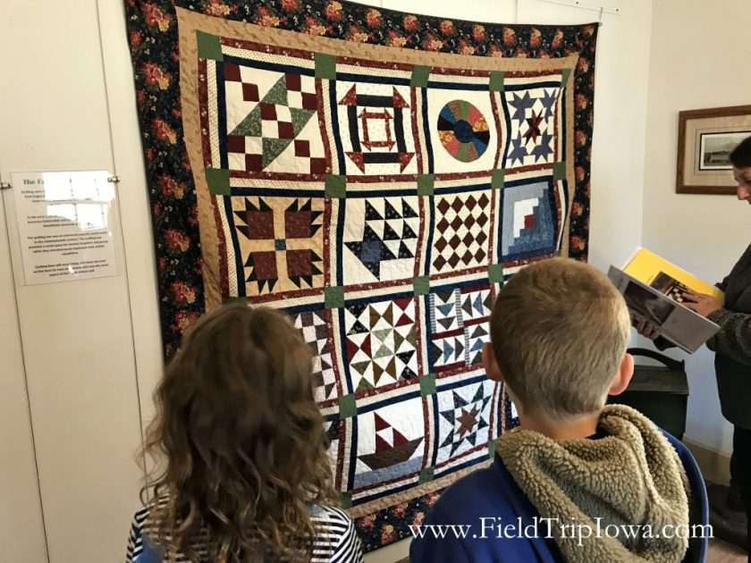 Children look at a quilt that communicates the underground railroad at the Jordan House in West Des Moines