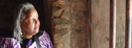 """Carol Hector-Harris reflects on her heritage as she gazes out """"the door of no return"""" at the Elmina slave fort in Ghana. """"What a God-awful, infamous place,"""" she said."""