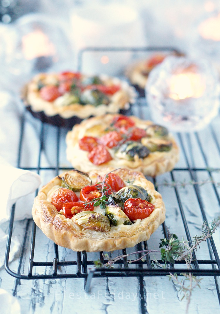 This Brussels Sprouts Cherry Tomato Tart is the perfect Christmas appetizer. The round red and green-colored vegetables are like Christmas ornaments nestled on a creamy and cheesy bed with a crispy puff pastry shell! - FiestaFriday.net #appetizer #christmas #tart #cheese #fontina #ricotta #brusselssprouts #cherrytomato