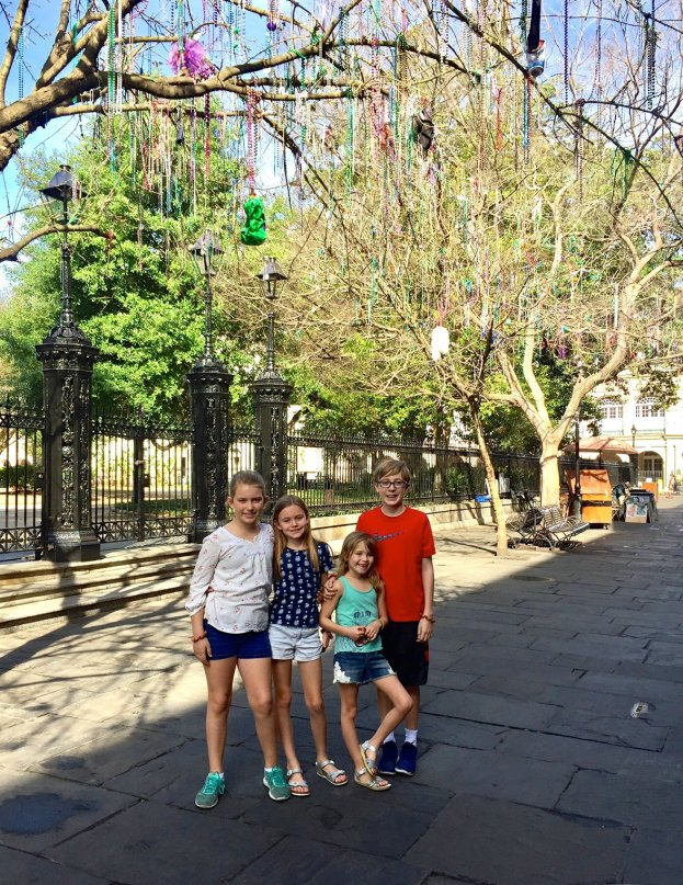 Kids underneath hanging mardi gras beads in Jackson Square in the French Quarter in New Orleans.
