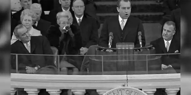 """President Richard M. Nixon dedicates his new administration to the cause of """"peace among nations"""" as former President Lyndon Johnson, right, listens to the inaugural speech Jan. 20, 1969 in Washington. Seated at right is Vice President Spiro Agnew and former Vice President Hubert Humphrey."""