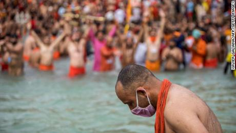 A Sadhu wearing a face mask takes a holy dip in the Ganges River during the Kumbh Mela festival in Haridwar, India, on April 12.