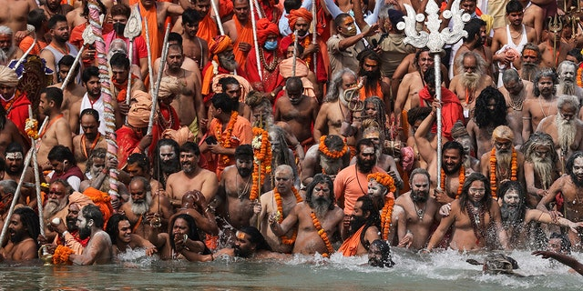 April 12, 2021: Naked Hindu holy men take holy dips in the Ganges River during Kumbh Mela, or pitcher festival, one of the most sacred pilgrimages in Hinduism, in Haridwar, northern state of Uttarakhand, India.