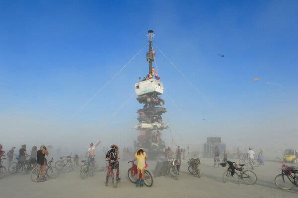 """Participants at Burning Man climbed onto an art installation titled """"Night of the Climb"""" in 2018. Organizers said on Tuesday that the annual festival would resume in 2022."""