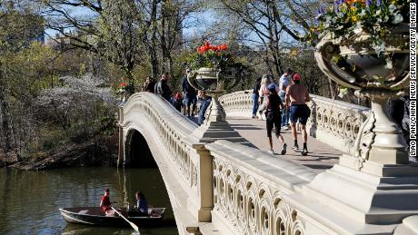 People stand on the Bow Bridge at Central Park on April 13, 2021 in New York City. The city is targeting a July 1 reopening.