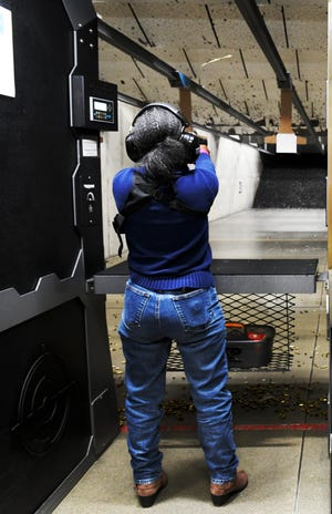 An ejected bullet casing flies over DeeAnn Pilate's head during firearms training held by the African American Gun Association at CrossRoads Shooting Sports in Johnston, Iowa, on Feb. 20, 2021.