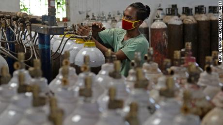 A worker fills medical oxygen cylinders on the outskirts of Chennai.