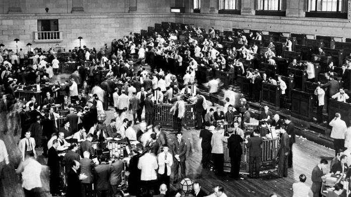 Traders rush in 1929 as the New York Stock Exchange crashes, sparking a run on banks.