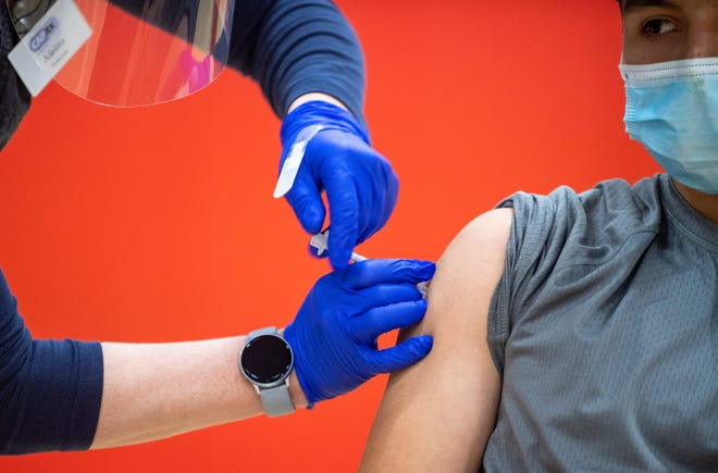 A high school student in Salinas receives his first dose of the Pfizer vaccine at North Salinas High School in Salinas Calif., on Thursday, April 15, 2021.