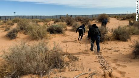 A smuggler leads two migrants toward the wall on the US-Mexico border in Ciudad Juárez, Mexico, dragging the makeshift ladder.