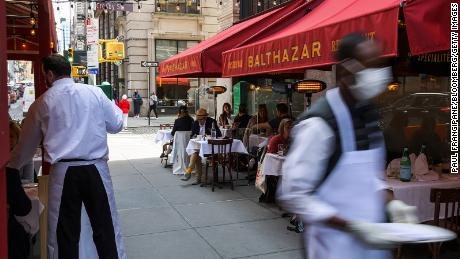 Customers dine on an outdoor patio in New York on April 27, 2021