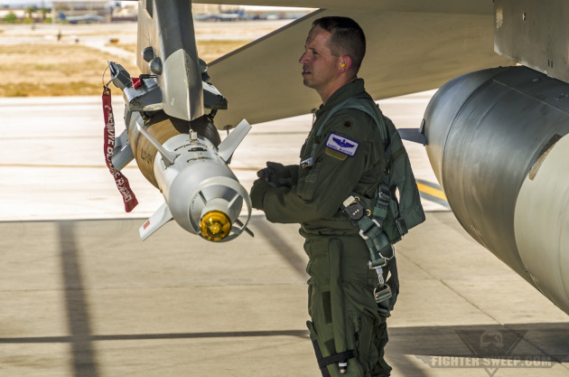 "Major Daniel ""Tank"" McAffee, pilot with the 55th Fighter Squadron, checks the pylon holding a live GBU-12 Paveway II laser-guided bomb under the wing of a Block 50 F-16CJ."