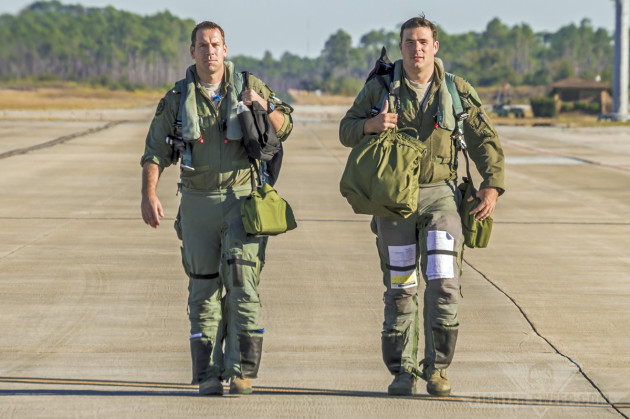 """Hypr"" and ""Ox,"" two F-16CJ pilots with the 55 FS (Roll 'Em!), walk back to briefing after returning from their training mission. Note both pilots are wearing the Advanced Technology Anti-G Suit (ATAGS)."
